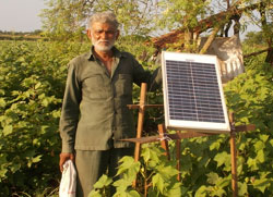 Shiyal bhai proudly standing beside his Zhataka Machine's solar panel which has reduced the menace of wild animals to almost cent percent
